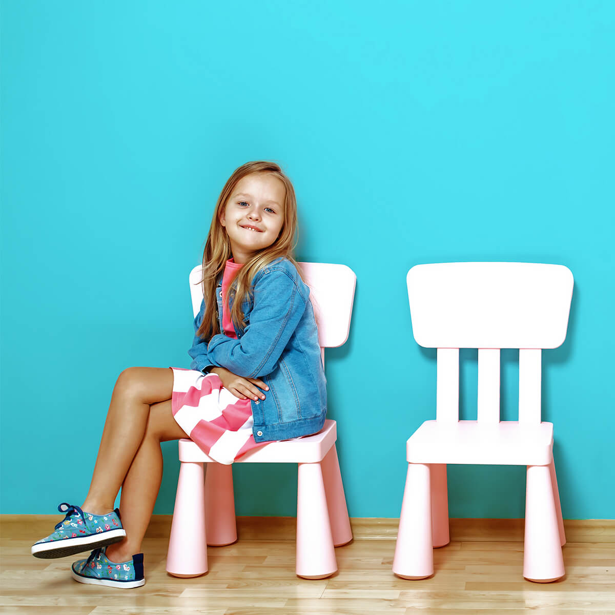 girl sitting in child-sized white chair