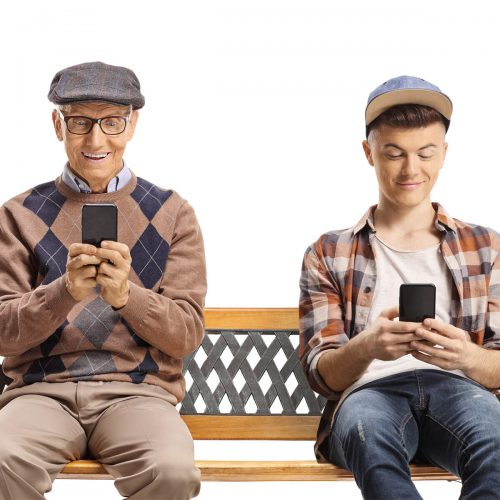 elderly and adolescent males looking at phones on bench