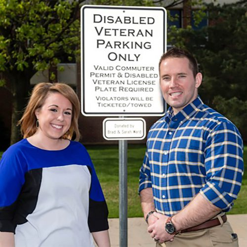 male and female veteran in front of disabled veteran parking sign