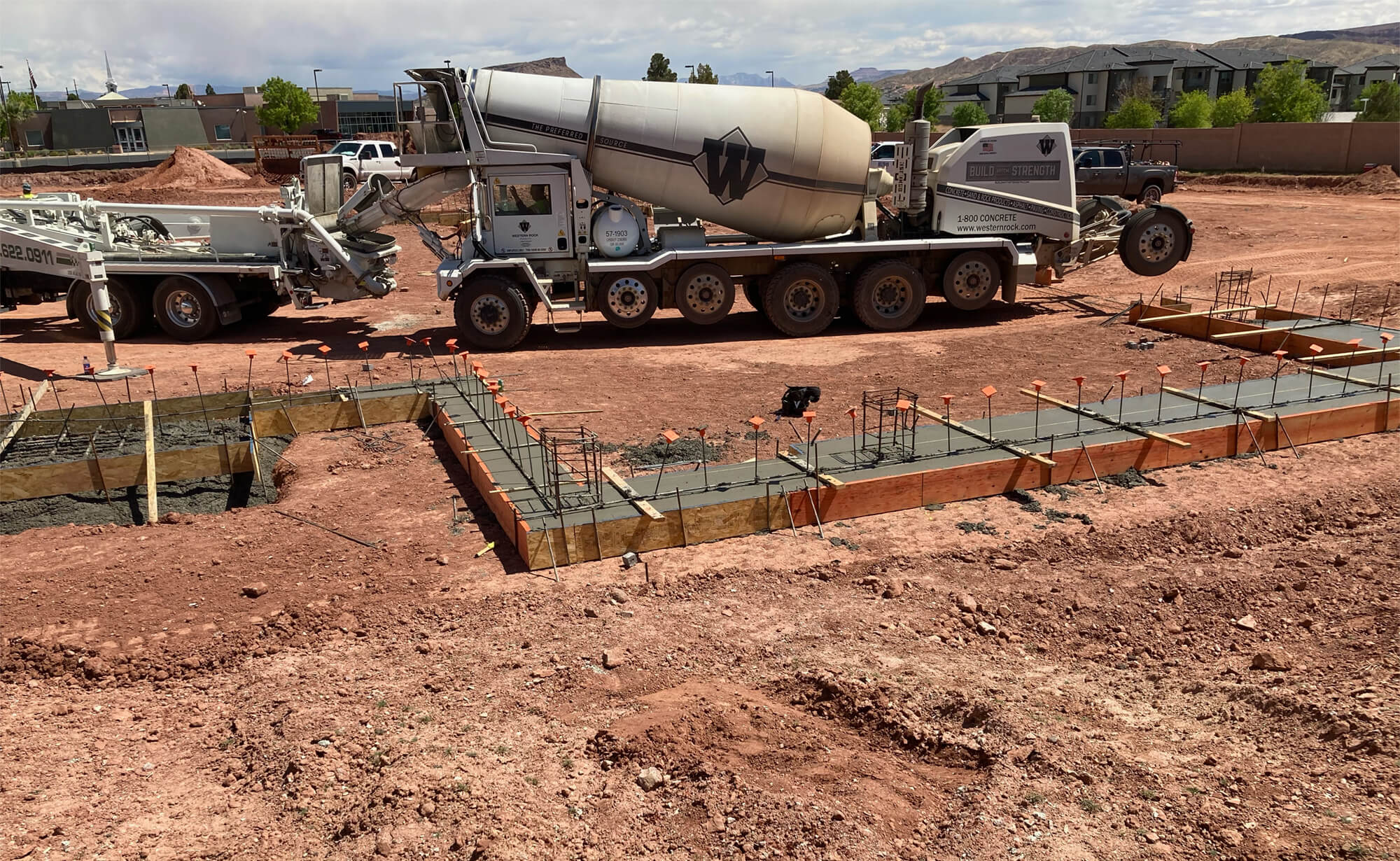 concrete truck loading concrete into pump to pour footings at the Riverside Clinic